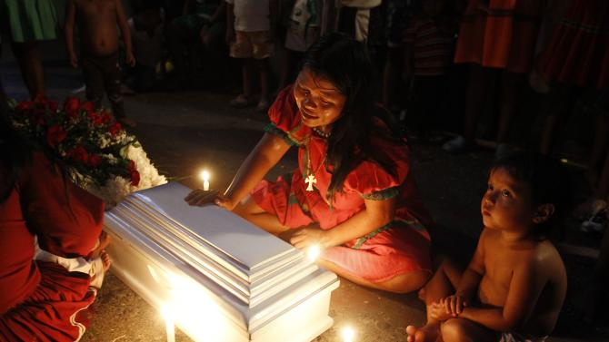 Queragama cries beside the coffin of her four-month-old daughter who died in Cali