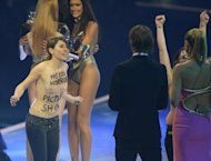 "Two activists of the Femen feminist group protest on stage during the final of Heidi Klum's (R) ""Germany's Next Topmodel"" TV show in Mannheim, southern Germany on May 30, 2013. Two bare-breasted female protesters burst on to the stage during the final hoted by Klum late Thursday"