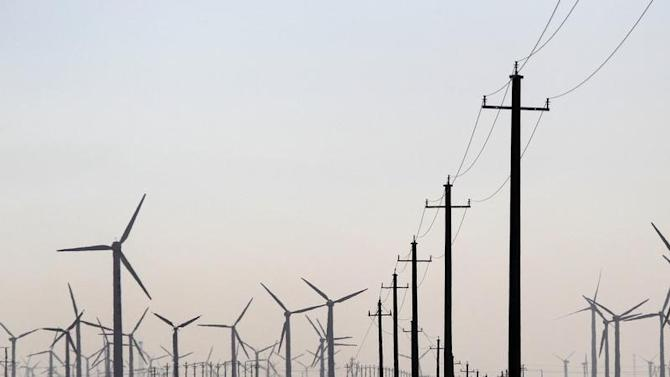 Windmills and electricity pylons are seen at the Xinjiang Tianfeng ...
