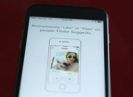 Photo illustration of dating app Tinder shown on an Apple iPhone