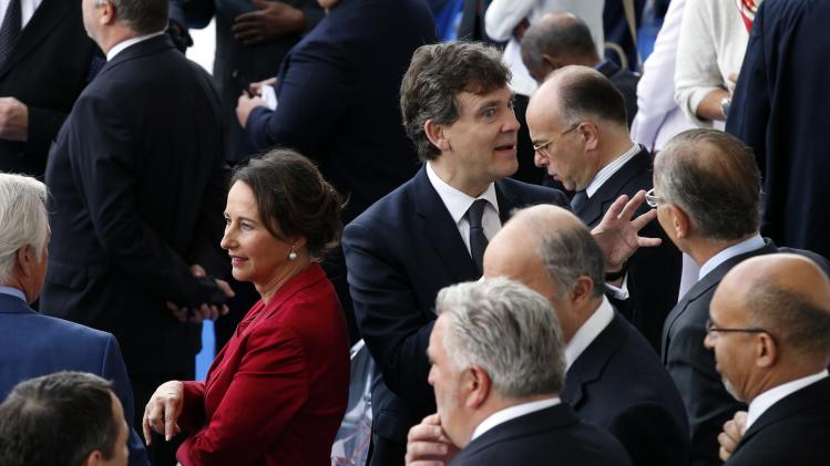 French minister for Ecology, Sustainable Development and Energy Segolene Royal and Economy Minister Arnaud Montebourg attend the traditional Bastille Day parade on the Champs Elysees avenue in Paris