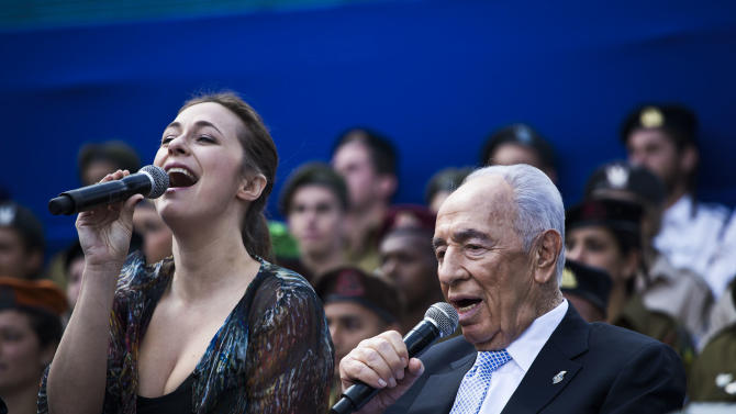 Israeli President Shimon Peres, sings with a singer during Israel's Independence Day celebration in Jerusalem, Israel, Tuesday, April 16, 2013. Israel is celebrating 65 years of independence with barbeques, air force flyovers, and a bible quiz. (AP Photo/Llia Yefimovich, Pool)