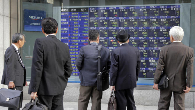 People look at an electronic stock board of a securities firm in Tokyo, Friday, Oct. 26, 2012. Asian stock markets fell Friday after the latest data on U.S. housing dimmed hopes of improvement in an industry that is crucial to recovery in the world's No. 1 economy. Japan's Nikkei 225 index fell 0.9 percent to 8,973.97. (AP Photo/Koji Sasahara)