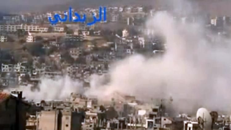 In this image taken from video obtained from the Shaam News Network, which has been authenticated based on its contents and other AP reporting, smoke rises from buildings due to government shelling in the Damascus suburb of Zabadani, Syria, on Friday, Nov. 23, 2012. At the same time, Syrian forces are raiding another neighborhood showing how fighting is spreading in Damascus, once a stronghold of President Bashar Assad. (AP Photo/Shaam News Network via AP video)