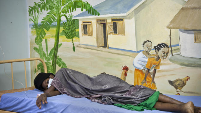 A newly-diagnosed HIV positive woman, who arrived at the hospital with symptoms of tuberculosis (TB), lies in the treatment ward of the Mildmay Uganda clinic, which receives funding from the US government through the Centers for Disease Control and Prevention (CDC), in Kampala, Uganda Thursday, Feb. 27, 2014. Uganda's government has been hit with substantial aid cuts after the president enacted a severe anti-gay measure over which some Western governments had warned of consequences, and at least three European countries are withdrawing millions in direct support to Uganda's government, which depends on donors for about 20 percent of its budget. (AP Photo/Rebecca Vassie)