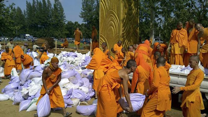 Buddhist monks pile up sand bags to make flood barriers at Dhamagaya temple in Pathum Thani province, central Thailand Tuesday, Oct. 18, 2011. Soldiers, civil servants and families worked frantically Tuesday to add more than 1 million sandbags to Bangkok's vulnerable northern flood defenses after the city's governor warned they were needed to keep waters from swamping the capital. (AP Photo)