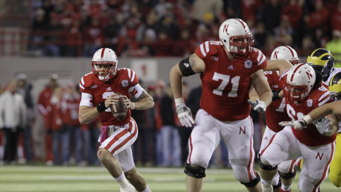 In this Oct. 27, 2012, photo, Nebraska quarterback Taylor Martinez (3) carries the ball behind Jeremiah Sirles (71) and Spencer Long (61) in an NCAA college football game against Michigan in Lincoln, Neb. UCLA plays at Nebraska on Sept. 14. The Bruins made a statement early last season in Los Angeles by beating the Cornhuskers 36-30. Quarterback Brett Hundley and the Bruins put up 653 yards against Nebraska. Now the Bruins come to Lincoln with the Huskers looking for payback and with one of the most versatile and dynamic offenses in the country, led Martinez. (AP Photo/Nati Harnik)