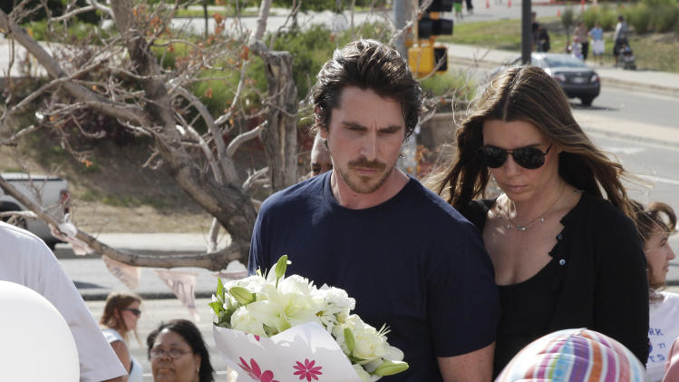 """Actor Christian Bale and his wife Sibi Blazic carry flowers as they visit a memorial to the victims of Friday's mass shooting, Tuesday, July 24, 2012, in Aurora, Colo. Twelve people were killed when a gunman opened fire during a late-night showing of the movie """"The Dark Knight Rises,"""" which stars Bale as Batman. (AP Photo/Ted S. Warren)"""