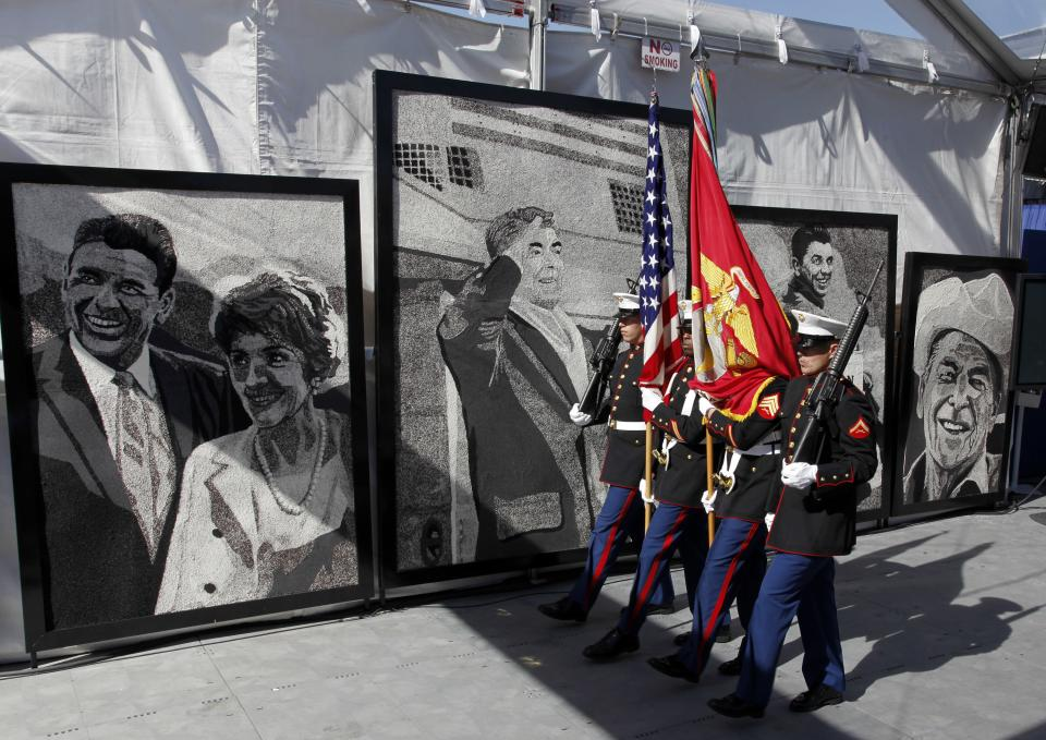 A military honor guard passes large portraits of former U.S. President Ronald Reagan and first lady Nancy Reagan during the centennial birthday celebration in Simi Valley, Calif, on Sunday Feb. 6, 2011. (AP Photo/Richard Vogel)
