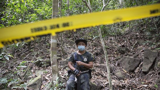 A policeman monitors as forensic experts dig out human remains near the abandoned human trafficking camp in the jungle close the Thailand border at Bukit Wang Burma in northern Malaysia