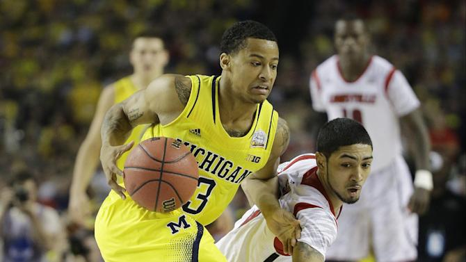 Louisville guard Peyton Siva (3) and Michigan guard Trey Burke (3) work during the second half of the NCAA Final Four tournament college basketball championship game Monday, April 8, 2013, in Atlanta. (AP Photo/David J. Phillip)