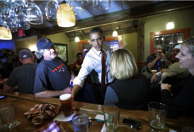 President Barack Obama reaches for his beer from the bar as he greets local patrons during an unscheduled visit to the Common Man Merrimack restaurant, Saturday, Oct. 27, 2012 in Merrimack, NH. (AP Ph