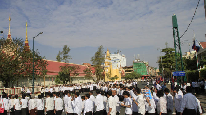 Mourners line up outside the cremation site before they enter to offer prayers for Cambodian late former King Norodom Sihanouk near the Royal Palace in Phnom Penh, Saturday, Feb. 2, 2013. Sihanouk's body had been lying in state at the Royal Palace after being flown from Beijing where he died Oct. 15 of a heart attack at the age of 89. The cremation, the climax of seven days of mourning, will take place Monday. (AP Photo/Heng Sinith)