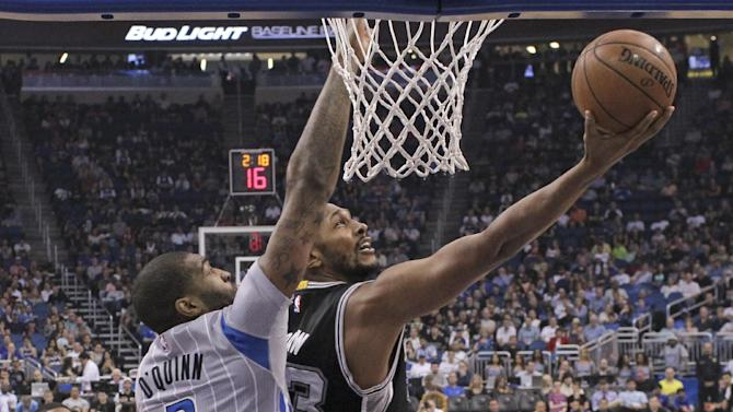 San Antonio Spurs' Boris Diaw, right, makes a shot as he is defended by Orlando Magic's Kyle O'Quinn (2) during the first half of an NBA basketball game, Wednesday, April 1, 2015, in Orlando, Fla. (AP Photo/John Raoux)