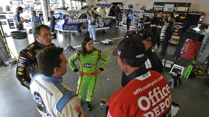 Tony Stewart, front left, Ryan Newman, back left, and Danica Patrick, back center, talk to crew members during practice for Sunday's NASCAR Daytona 500 auto race in Daytona Beach, Fla., Wednesday, Feb. 22, 2012. (AP Photo/Rainier Ehrhardt)