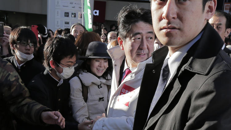 "In this Tuesday, Dec. 11, 2012 photo, Japan's main opposition Liberal Democratic Party President Shinzo Abe, second from right in white, shakes hands with supporters during a campaign rally for the Dec. 16 parliamentary elections in Machida, on the outskirts of Tokyo. The buzz over Japan's parliamentary elections this Sunday, Dec. 16, has been all about ""the third force"" - a clear sign of the prevailing disenchantment over both the party that ruled for decades after World War II and the rival party that took over in 2009.  (AP Photo/Itsuo Inouye)"
