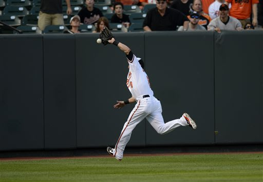Baltimore Orioles left fielder Nate McLouth (9) can't handle a fly ball hit by New York Yankees' Brett Gardner for a double in the first inning of a baseball game, Tuesday, May 21, 2013, in Baltimore