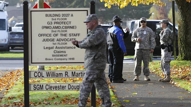 Soldiers and security officers stand Monday, Nov. 5, 2012, outside the building housing a military courtroom on Joint Base Lewis McChord in Washington state, where a preliminary hearing began Monday for U.S. Army Staff Sgt. Robert Bales. Bales is accused of 16 counts of premeditated murder and six counts of attempted murder for a pre-dawn attack on two villages in Kandahar Province in Afghanistan last March. (AP Photo/Ted S. Warren)