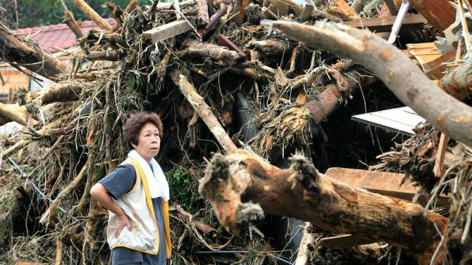 Woman reacts in front of collapsed houses following a landslide caused by Typhoon Wipha on Izu Oshima island