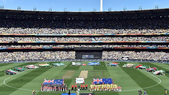 Australian and New Zealand cricketers stand for the national anthems during the 2015 Cricket World Cup final in Melbourne on March 29, 2015