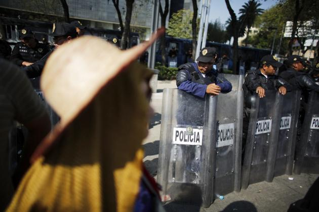 Riot policeman pauses while guarding the Sentae building during a protest against the energy reform outside the Senate building in Mexico City