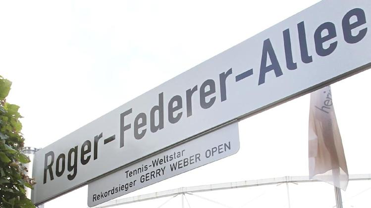 Swiss tennis player  Roger Federer , left, passes a street plate with his name prior to the final tennis match of the Gerry Weber Open ATP tournament between Roger Federer and German Tommy Haas in Halle, western Germany, Sunday June 17, 2012. ( (AP Photo/dapd/Joerg Sarbach)
