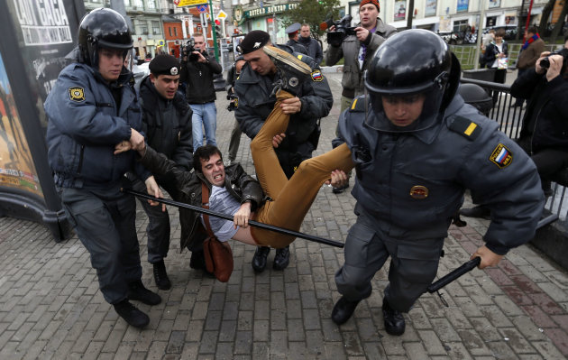 Police officers detain political activist Roman Dobrokhotov during the unauthorized meeting to mark Russian President Vladimir Putin's birthday in Moscow, Sunday Oct. 7, 2012. Vladimir Putin turns 60-