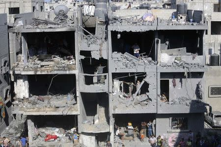 Palestinians standing in a badly damaged house watch rescue workers as they search for victims in Rafah