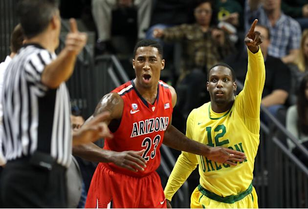 Arizona's Rondae Hollis-Jefferson, center, reacts to an official's call as Oregon's Jason Calliste, left, mirrors the call on an out-of-bounds play that went in favor of the Ducks during t