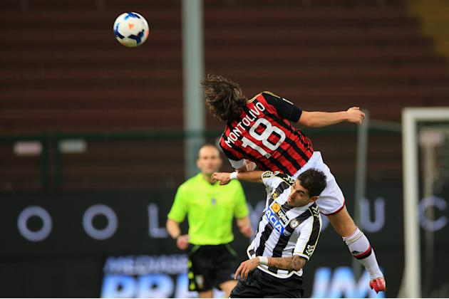 AC Milan's Riccardo Montolivo, top, and Udinese's Roberto Pereyra challenge for the ball during the Serie A soccer match between Udinese and AC Milan at the Friuli Stadium in Udine, Italy, Sat