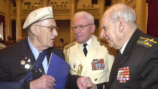 FILE - This is a Wednesday, May 4, 2005 file photo of  British World War II veteran, participant of Arctic convoys, Raymond Ball, left speaks with Russian veterans Anatoly Uvarov, center, and Anatoly Livshits in St.Petersburg, Russia, Dozens of British and Russian sailors of the Arctic convoys that dodged German U-boats to bring supplies to the Soviet Union during World War II gathered in St. Petersburg Wednesday to trade memories and mark the anniversary of the Allied victory of the Nazis. Thousands of British  veterans who sailed on Arctic convoys to support the Russian war effort have been told they cannot collect bravery medals. Those who took part have now been offered Ushakov medals by the Russian government to recognise their extreme courage. But they have been told by Britain's   Foreign and Commonwealth Office Monday Jan. 14, 2013 that accepting the medals would break rules in this country.(AP Photo/Dmitry Lovetsky, File)