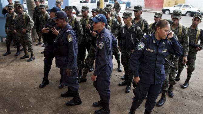 In this June 1, 2013 photo, Honduras National Police officers and Honduras Army soldiers prepare for a patrol in the John F. Kennedy neighborhood in Tegucigalpa, Honduras. The government of Honduras launched an unprecedented effort last year to clean up a U.S.-backed police force widely seen as deeply brutal and corrupt. One by one, hundreds of police officers were subjected to polygraph tests administered by Colombian technicians funded by the U.S. government. Nearly four of every 10 officers failed the test in the first five months it was administered, some giving answers that indicated that they had, among other violations, tortured suspects, accepted bribes and taken drugs, according to a confidential U.S. document provided to The Associated Press. (AP Photo/Esteban Felix)