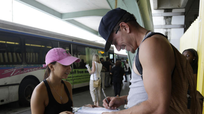 FILE - In this Sept. 25, 2013 file photo, Maygan Rollins, 22, a field organizer with Enroll America, left, talks with Jerry Correa, 27, about his health care options while canvassing at a bus stop in Miami. Enroll America is a private, non-profit organization running a grassroots campaign to encourage people to sign up for health care offered by the Affordable Care Act. Despite Florida Republicans' efforts to fight the Affordable Care Act at every turn, more than 440,000 Florida residents had been enrolled through the federal marketplace through the end of February. (AP Photo/Lynne Sladky, File)