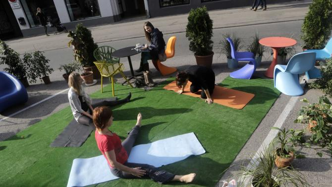 People practice yoga during the PARK(ing) Day event in Riga