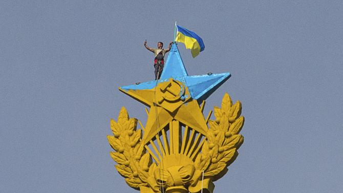 """A man takes a """"selfie"""" as he stands with a Ukrainian flag on a Soviet-style star re-touched with blue paint so it resembles the yellow-and-blue national colours of Ukraine, atop the spire of a building in Moscow"""