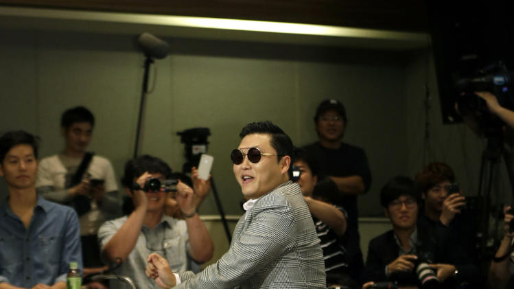 "South Korean rapper PSY, who sings the popular ""Gangnam Style"" song, dances as he leaves his press conference in Seoul, South Korea, Tuesday, Sept. 25, 2012. (AP Photo/Lee Jin-man)"