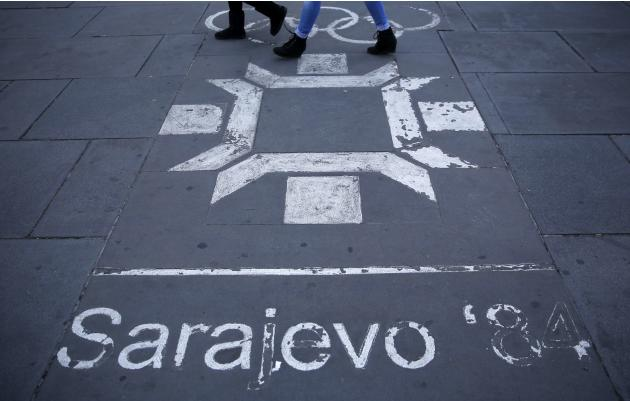 People walk past the logo of the Winter Olympics in Sarajevo, painted on the streets in central Sarajevo