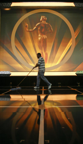 A worker sweeps the stage as setup for the SAG Awards is under way at the Shrine Auditorium in Los Angeles on Saturday, Jan. 28, 2012. (AP Photo/Jason Redmond)