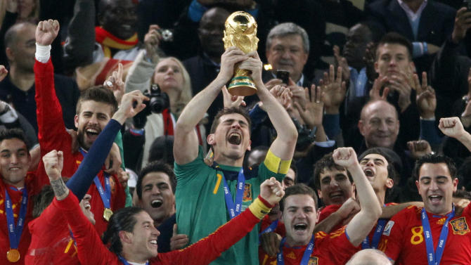 """FILE _ This is a file photo of Spain's goalkeeper Iker Casillas, center, as he holds up the World Cup trophy with team members as they celebrate their victory at the end of the World Cup final soccer match between the Netherlands and Spain at Soccer City in Johannesburg, South Africa. Winning the soccer World Cup can bring instant rewards to that country's stock market investors. But they better be quick as the post-victory rally doesn't last long. That's the conclusion of investment bank Goldman Sachs, which published a wide-ranging report late Tuesday May 27, 2014 on the World Cup and its economic impact. Goldman Sachs analysts found """"a clear pattern of out performance by the wining team in the weeks after the World Cup final."""" On average, the investment bank's portfolio strategy team the victor outperforms the global market by 3.5 percent in the first month. (AP Photo/Luca Bruno, File)"""