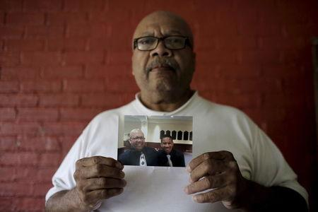 Ronald Cook, holds a photograph of him and his 20-year-old grandson Devin Cook, who was killed last year, at his home in Baltimore, Maryland