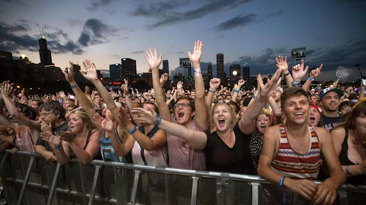 FILE - This Aug. 3, 2013 file photo shows fans reacting while Mumford & Sons performs at the Lollapalooza Festival in Chicago. Lollapalooza marks its 10th anniversary in Chicago when it opens for three days starting Friday, Aug. 1, 2014, with a lineup including Eminem, Outkast and Kings of Leon. Lollapalooza became the basis for the modern festival culture and circuit that has evolved since, including events like Bonnaroo, Coachella and a legion of smaller multi-day parties. (AP Photo/Scott Eisen, File)