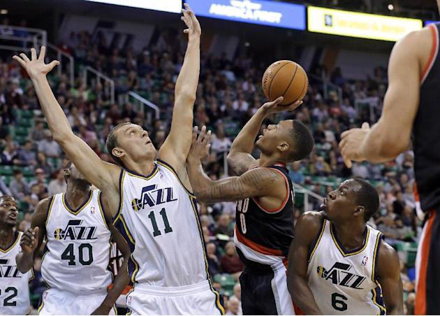 Portland Trail Blazers' Damian Lillard (0) shoots as Utah Jazz's Andris Biedrins (11) defends while Utah'sLester Hudson (6) watches duringthe second quarter of an NBA preseason basketball game Wednesd