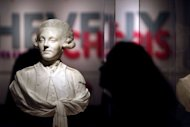A visitor looks at a statue displayed during the exhibition, &quot;Cheveux Cheris&quot; at the Quai Branly Museum in Paris. Forget the cliche of the wild-haired caveman: &quot;Humans have cut, arranged and coiffed their hair since at least 21,000 BC,&quot; explains Yves Le Fur, curator of the 10-month show