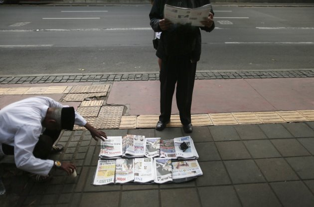 Morning commuter reads a newspaper he bought from a sidewalk newspaper vendor in central Jakarta