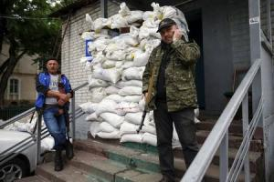 Members of a group of separatists stand outside an office in the town of Druzhkovka, Donetsk region