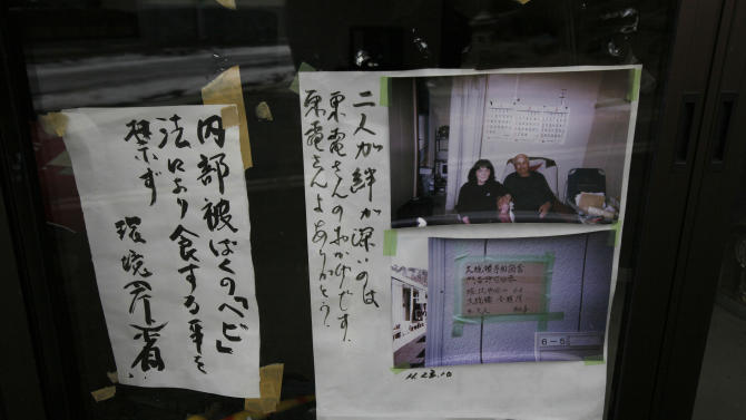 In this Monday, March 4, 2013 photo, protest slogans criticising Tepco, the company which ran the crippled Fukushima Dai-ichi nuclear plant, appear with a photo of residents on the window of the home they were forced to evacuate in Namie, outside the the nuclear exclusion zone surrounding the plant in Japan. Two years after a tsunami crippled the nuclear plant, towns surrounding it remain abandoned, too contaminated by radiation for residents to return for more than short visits.  (AP Photo/Greg Baker)