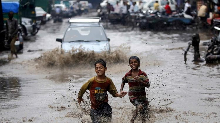 Boys run through a water logged street after heavy monsoon rains in New Delhi
