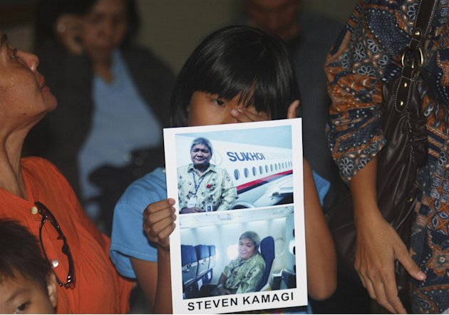 Tasya Kamagi, 10, holds the pictures of his father Steven that were taken when he boarded a Russian-made Sukhoi Superjet-100 that crashed on a mountainous area in West Java, at Halim Perdanakusuma Air