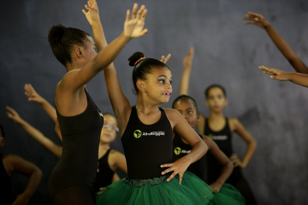 Young dancers from the Afro Reggae center perform before members of London&#39;s Royal Opera House in the Vigario Geral slum of Rio de Janeiro, Brazil, Saturday, March 2, 2013. This past week Royal Ballet dancers shared their knowledge and advice with promising artists during an education symposium between the company and the cultural arts center Afro Reggae. (AP Photo/Silvia Izquierdo)