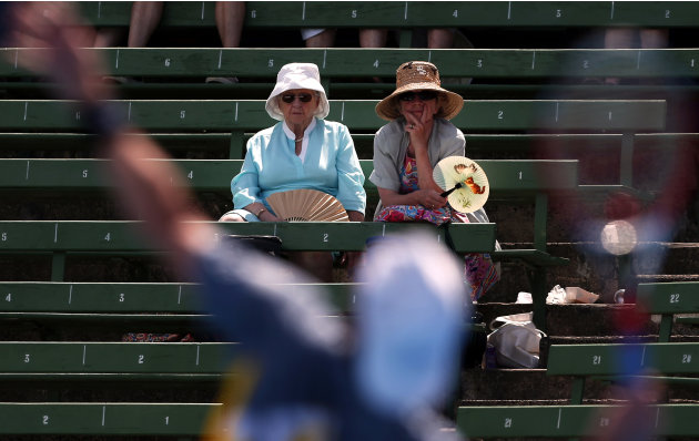 Two ladies with fans watch France's Mathieu serve during his match against Italy's Bolelli at the Kooyong Classic tennis tournament in Melbourne